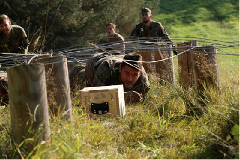 Ein Aufklärer schiebt seine Munitionskiste durch ein Drahthindernis